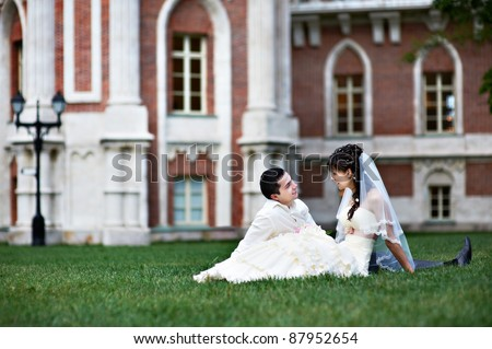 Happy bride and groom on lawn in front of palace - stock photo