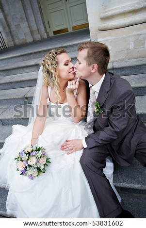 Happy bride and groom on stairs of palace in wedding day