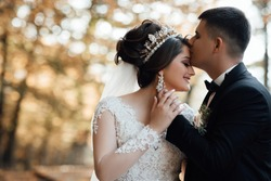 Happy bride and groom on their wedding. The groom kisses the forehead of the bride. Portrait of the bride. Newlyweds in the park. Happy couple. Wedding photo. Couple in love. Autumn wedding