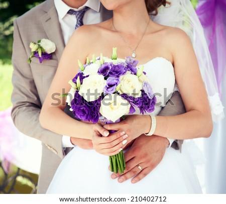 Happy bride and groom on their wedding. Wedding couple holding hands. Bride and groom holding hands. Wedding bouquet closeup. Fashionable toning. Selective focus