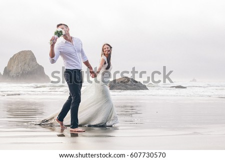 Happy bride and groom walk by the beach #607730570
