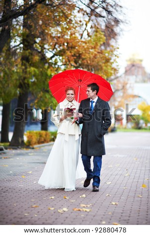 Happy bride and groom walking in yellow autumn park on wedding day