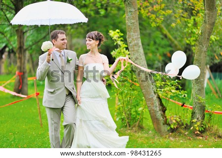 Happy bride and groom walking together in a park