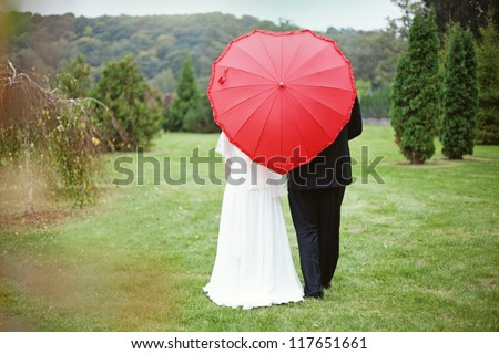 Happy bride and groom with the umbrella (soft focus, focus on umbrella)