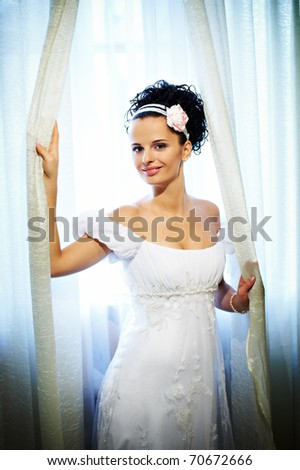 stock photo Happy bride in wedding dress near sunny window