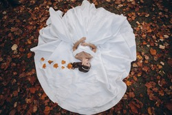 Happy bride on autumn forest. Bride in a white luxurious modern long dress. Elegant collected hairstyle with decoration, silver diadem twig. Autumn forest red leaves of trees