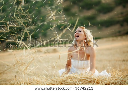 Happy bride playing with hey in field at her wedding day