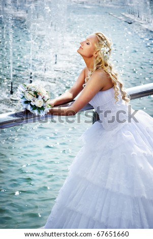 Happy bride with bouquet of flower at wedding walk in the park