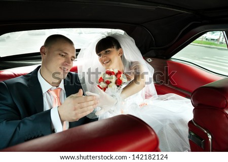 Happy bride with bouquet of flowers inside red car showing her ring to groom with selective focus - stock photo