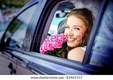happy bride with flower bouquet siting in the car