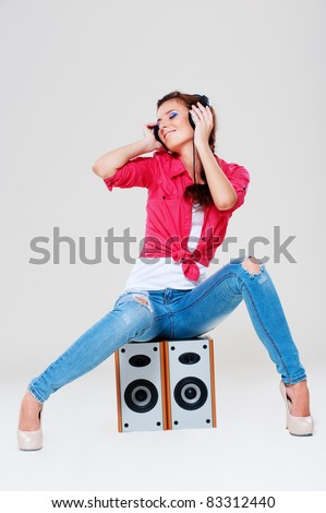 happy bright girl with headphones sitting on speakers
