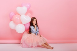 Happy brightful image of cute joyful little girl in tulle skirt sitting on present with balloons isolated on pink background. Amazing charming birthday fashionable kid looking to camera