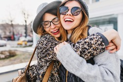 Happy brightful positive moments of two stylish girls hugging on street in city. Closeup portrait funny joyful attarctive young women having fun, smiling, lovely moments, best friends