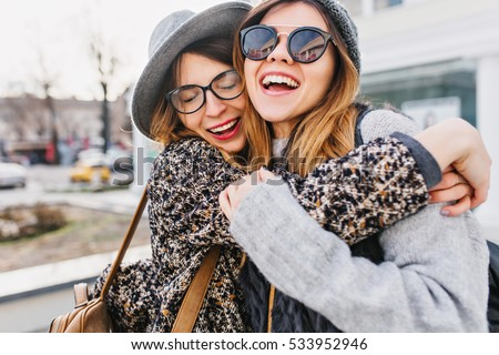 Happy brightful positive moments of two stylish girls hugging on street in city. Closeup portrait funny joyful attarctive young women having fun, smiling, lovely moments, best friends #533952946