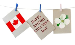 Happy British Columbia Day. Holiday greeting cards with Pacific dogwood flower - Floral emblem of B.C. and Canadian national flag. Festive cards hanging on the rope isolated on white