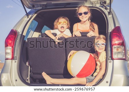 Happy brother and his two sisters are sitting in the car at the day time #259676957