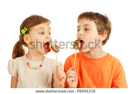 Happy brother and sister lick colorful lollipops isolated on white background