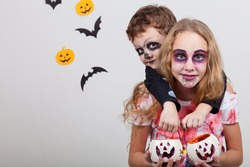 Happy brother and  sister on Halloween party. People having fun indoor. Children wearing costumes  skeletons and zombies. Concept of children ready for a party.