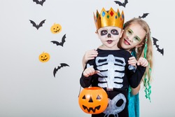 Happy brother and  sister on Halloween party. People having fun indoor. Children wearing costumes  skeletons and witches. Concept of children ready for a party.