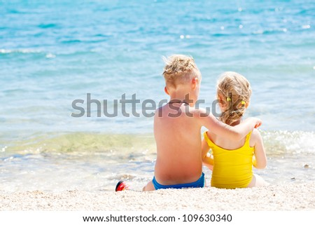 Happy brother and sister relaxing on the coast of the sea