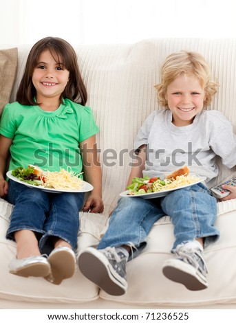 Happy brother and sister watching television while eating pasta and salad on the sofa