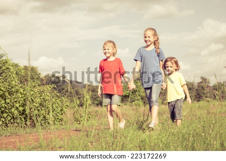 Happy brother and sisters running on the road at the day time. Concept of friendly family.