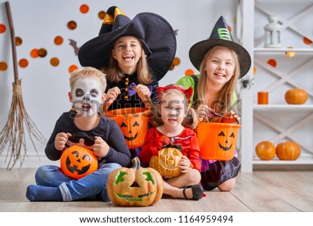 Happy brother and three sisters on Halloween. Funny kids in carnival costumes indoors. Cheerful children play with pumpkins and candy.