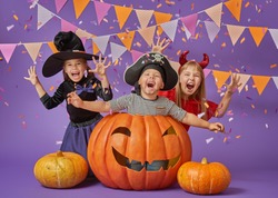 Happy brother and two sisters at Halloween. Funny kids in carnival costumes on background of purple wall. Cheerful children and pumpkins with confetti.