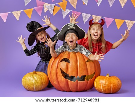 Happy brother and two sisters at Halloween. Funny kids in carnival costumes on background of purple wall. Cheerful children and pumpkins.