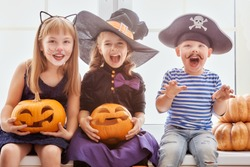 Happy brother and two sisters on Halloween. Funny kids in carnival costumes indoors. Cheerful children play with pumpkins.