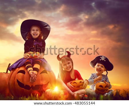 Happy brother and two sisters on Halloween. Funny kids in carnival costumes outdoors. Cheerful children and pumpkins on sunset background. #483055144