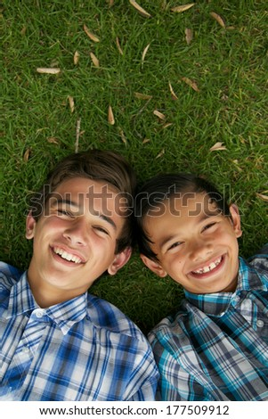 Happy brothers laying on the grass.