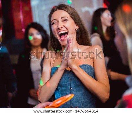 Happy brown hair sexy woman or girl in blue jeans dress naked shoulders takes birthday award win in hall cafe center restaurant night club party congratulations with other people on background indoor