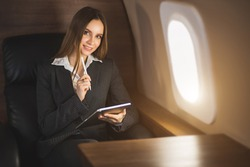 Happy brown haired young caucasian businesswoman holding tablet, sitting on seat in private jet, looking at airplane window and smiling.