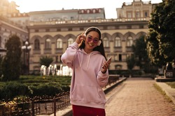 Happy brunette Asian woman in pink stylish hoodie and colorful sunglasses holds phone and listens to music in headphones outside.