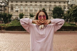 Happy brunette Asian woman smiles sincerely outside. Portrait of charming girl in pink hoodie and sunglasses.