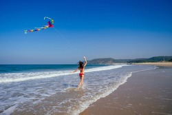happy brunette girl in a bathing suit and short pink playing with flying kite on tropical beach copyspase hills and mountains background