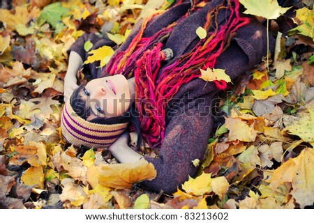 Happy brunette girl lying in autumn leaves. Outdoor.