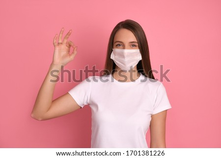Happy brunette girl wears a white medical mask to protect her from Corona virus, cares for her health and safety, has a smile, sticks to self-isolation, shows ok ring-gesture to be positive. Covid-19