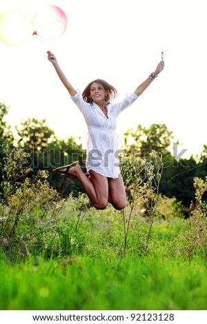Happy brunette girl with balloons relaxing in the field at sunset