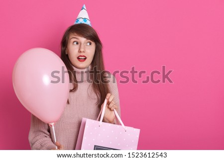 Happy brunette girl with pink balloon and bithday present in hands, keeps mouth opened, being in surprise, looks aside with astinished facial expression, copy space for advertisment or promotion.