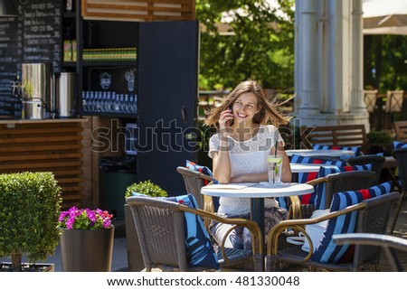 Happy brunette woman calling by phone in open air cafe