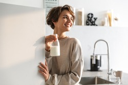 Happy brunette woman drinking milk and looking away while standing in kitchen