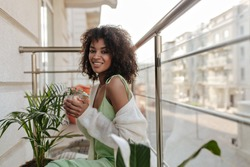 Happy brunette woman drinks coffee on balcony. Charming lady in light green dress smiles sincerely on terrace.