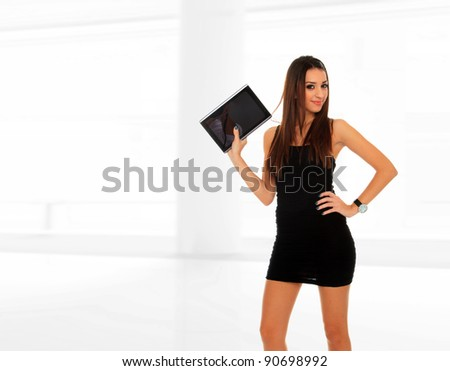 Happy brunette woman holding in hand a tablet touch pad computer at the office lobby