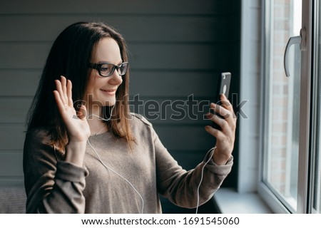 Happy brunette woman in glasses making facetime video calling with smartphone at home, using zoom meeting online app, social distancing, work from home, work remotely concept