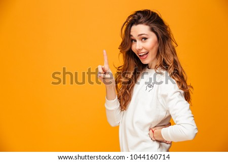 Happy brunette woman in sweater posing with arm on hip while having idea and looking at the camera over yellow background