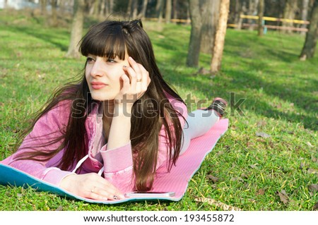 Happy brunette woman lying on the grass on a mat and enjoying the bright sunny day, dreaming about something