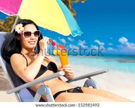 Happy brunette woman on vacation drinking orange juice on the beach