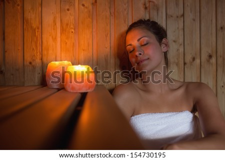 Happy brunette woman sitting in a sauna relaxing by candlelight